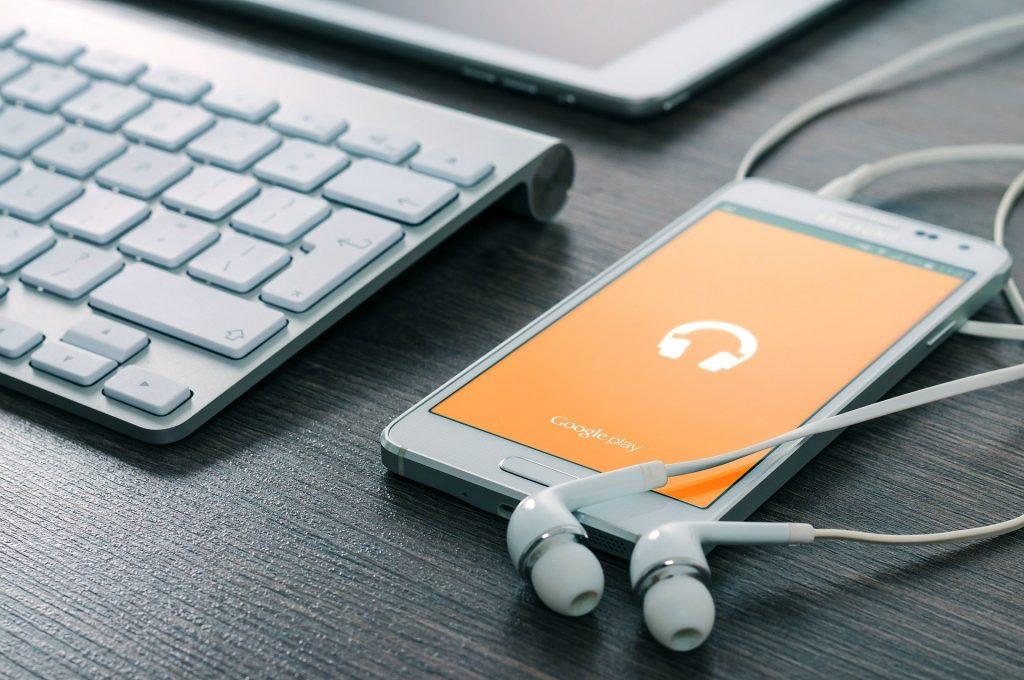 Celular Samsung com fone de ouvido conectado e notebook ao lado.