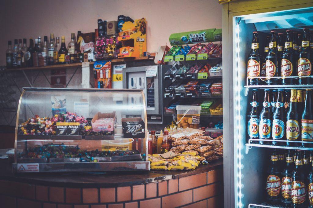Imagem mostra uma alta cervejeira vertical, repleta de garrafas de cerveja, ao lado do balcão de um bar, este repleto de pacotes de amendoim, balas e outros produtos.
