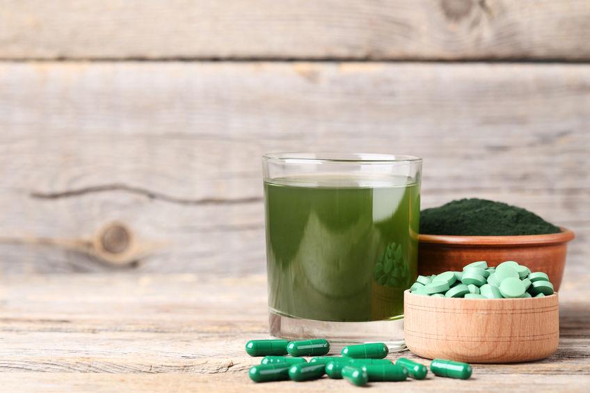 Chlorella em cápsulas, em pó e líquido verde no copo.
