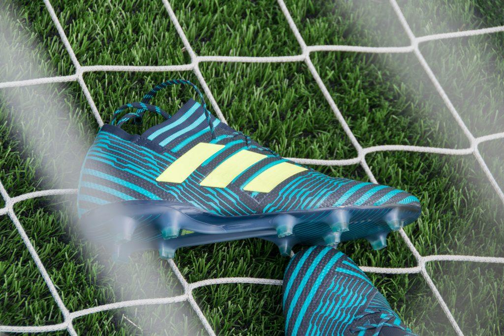 Imagem mostra um par de chuteiras deitados sobre uma rede de gol, que por sua vez está em cima da grama.