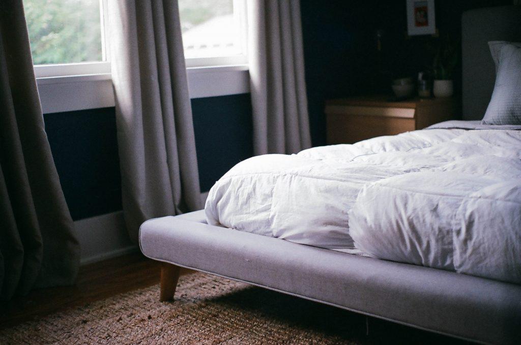 Imagem foca no pé de uma cama, com um colchão profundo apoiado sobre ele. O pé, por sua vez, está sobre um tapete, e ao lado de uma janela.