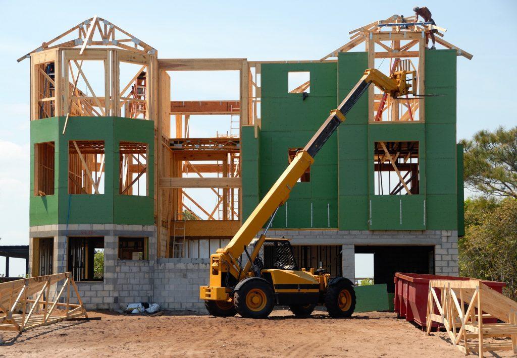 Trator em frente de uma casa em construção.
