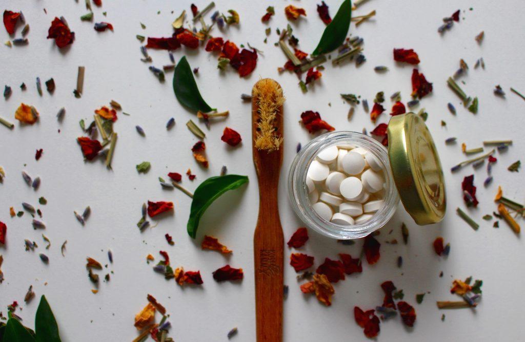 Imagem de escova de dente de bambu ao lado de pote com pílulas