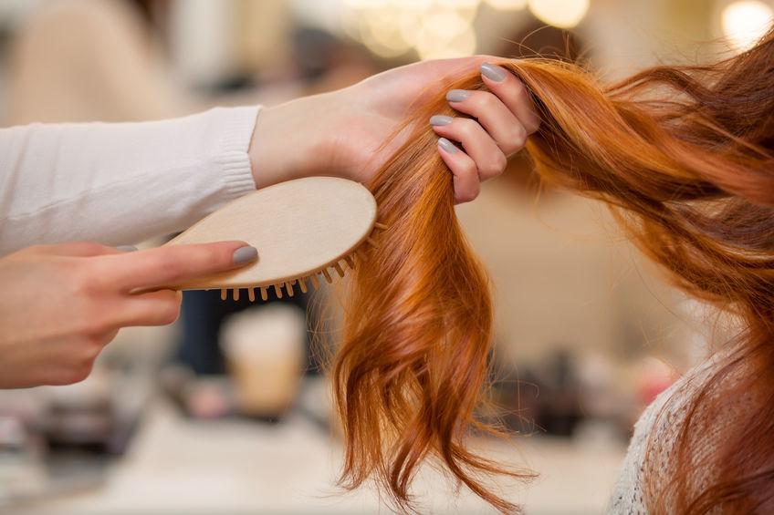 Mulher ruiva penteia as pontas dos cabelos