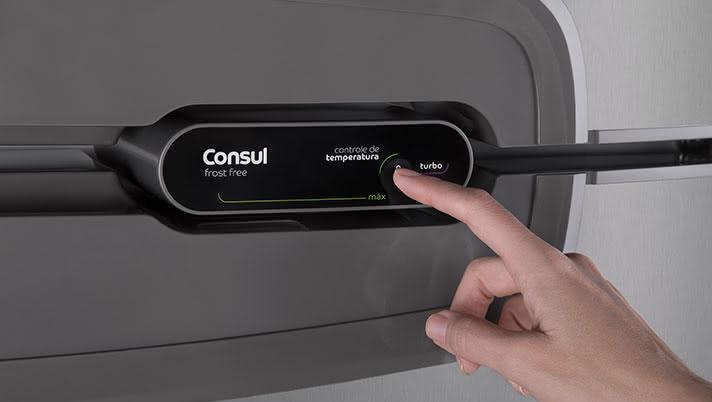 Imagem de pessoa acessando o painel touch de uma geladeira inox Consul
