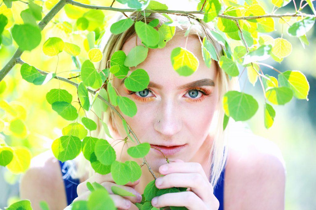 Foto de uma mulher loira, em meio a um arbusto, usando maquiagem alaranjada nos olhos.