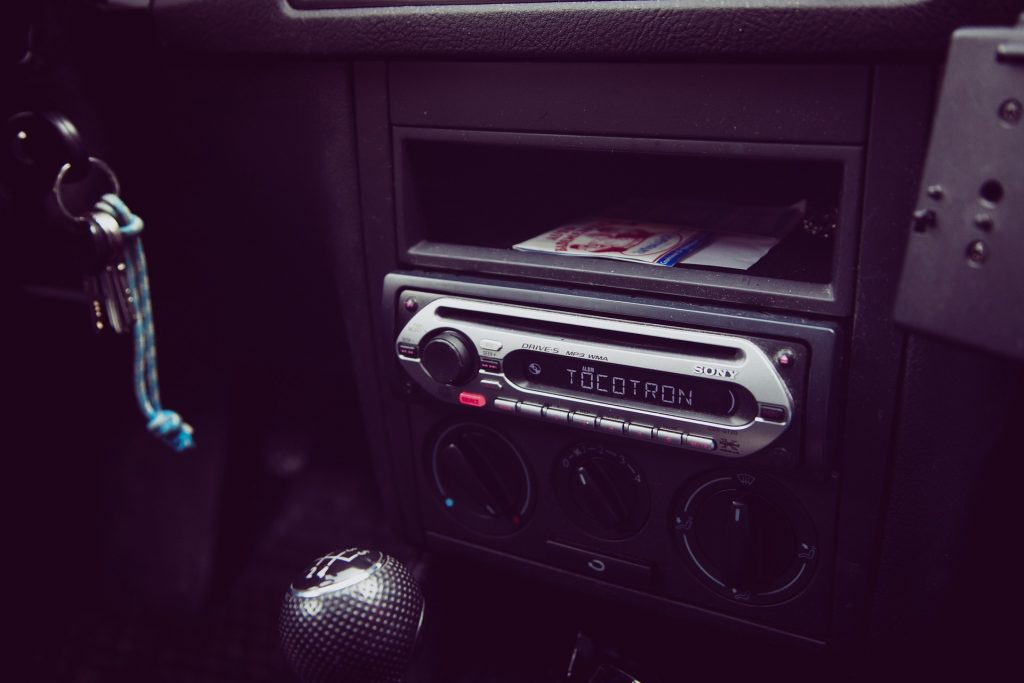 Imagem mostra um som automotivo instalado no painel de um carro e ligado, com um texto aparecendo em sua tela.