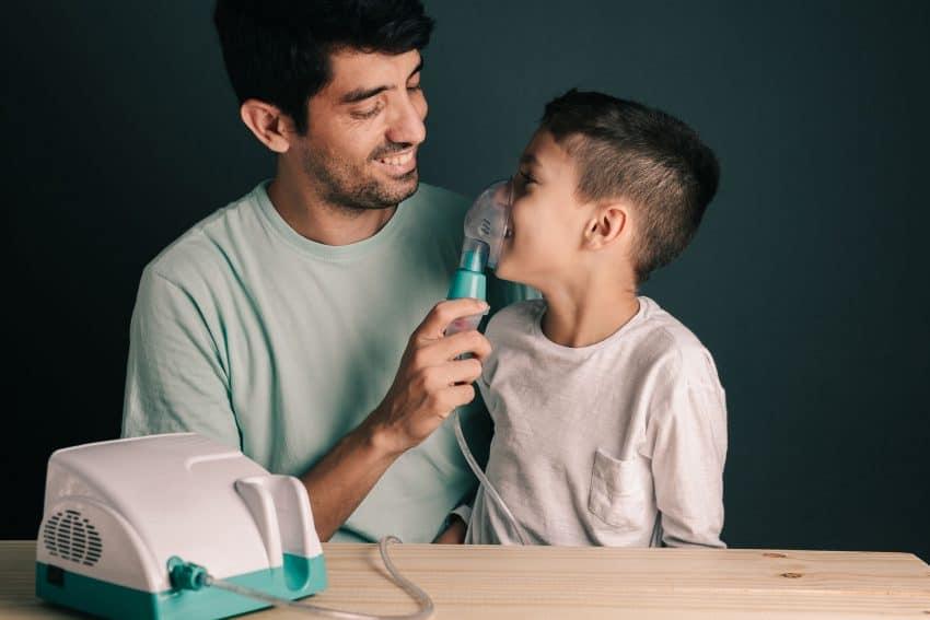 Na foto um homem fazendo nebulização em uma criança.