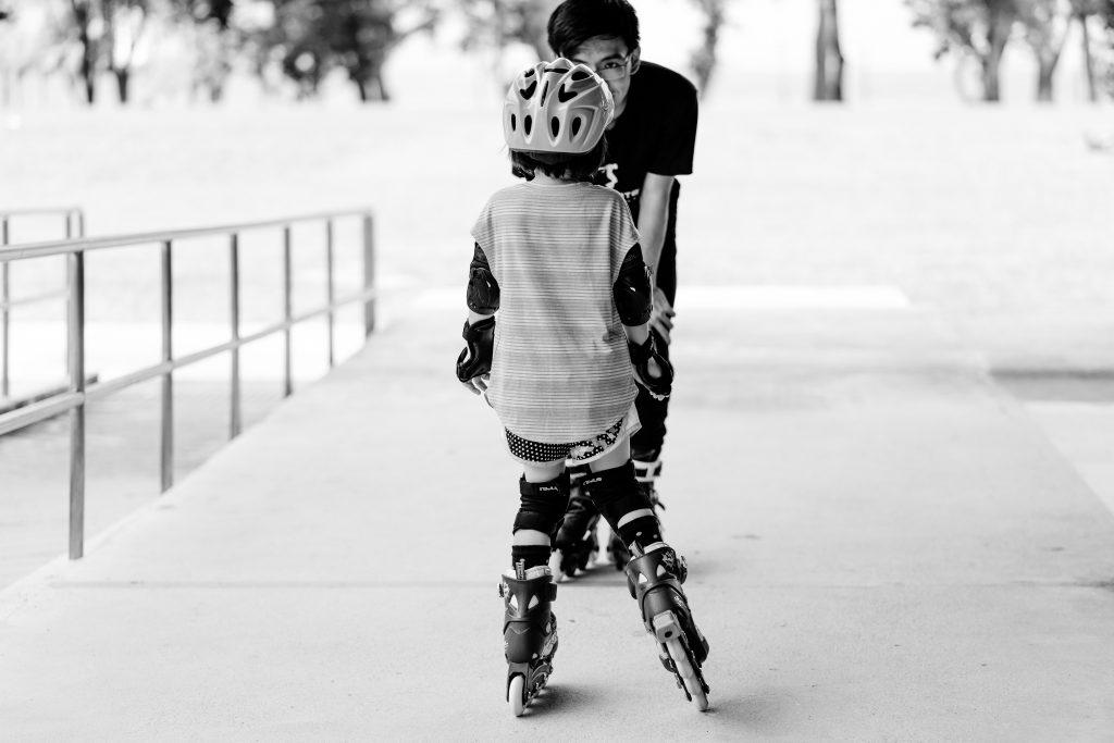 Imagem em preto e branco mostra uma criança de patins, de costas para a câmera, conversando com um adulto, que está abaixado, com as mãos no joelho e de frente para a câmera, encoberto parcialmente pela criança.