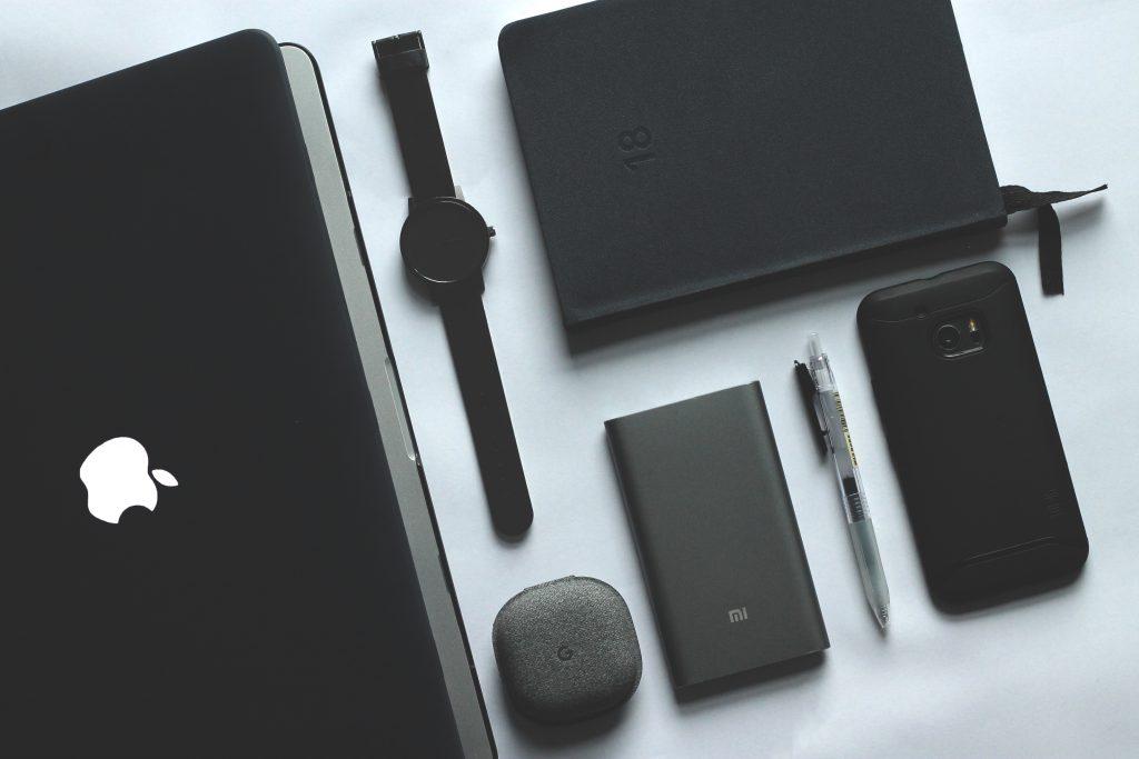 Imagem mostra uma composição com diversos itens sobre uma mesa, como celular, assistente eletrônico, relógio, e com um power bank Xiaomi numa posição central.