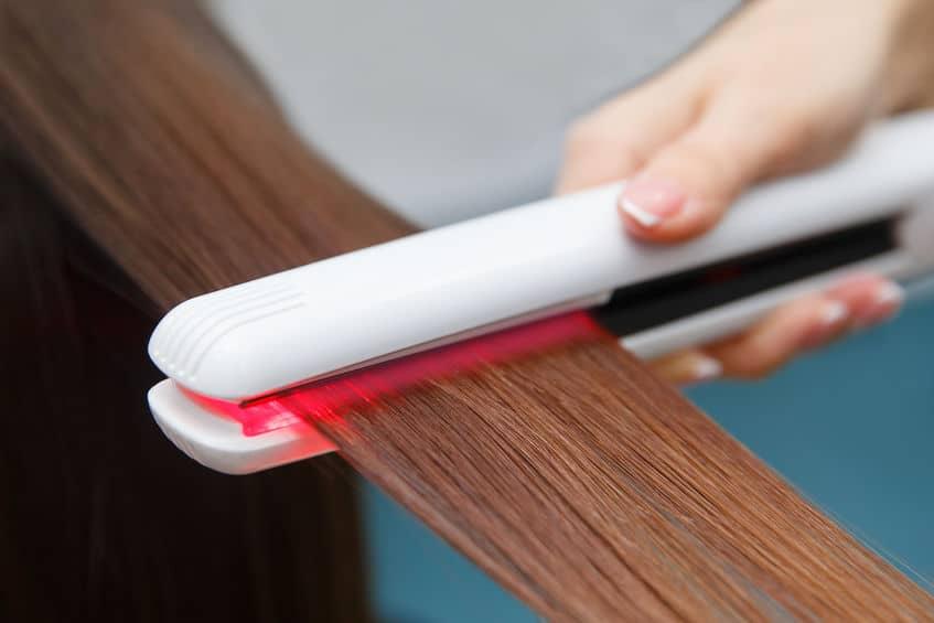 Na foto uma pessoa passando uma chapinha em uma mecha de cabelo.