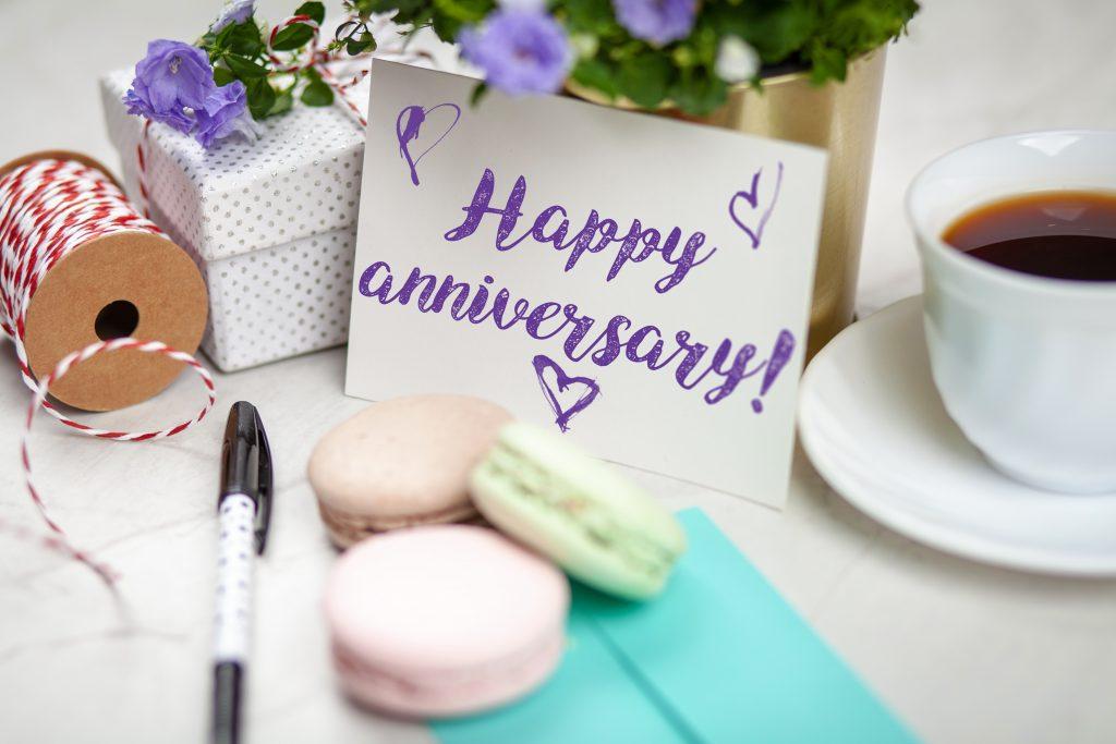 Na foto uma mesa com alguns itens e um cartão escrito feliz aniversário em inglês.