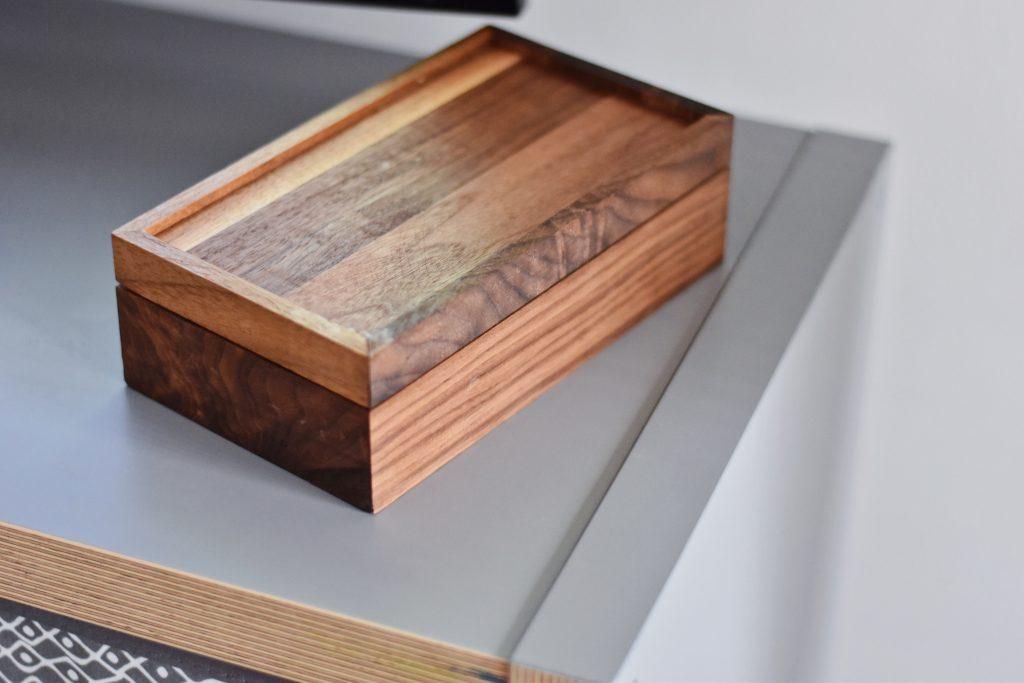 Imagem mostra uma caixa de madeira retangular, tampada, sobre um balcão.