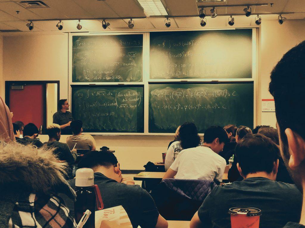 Na foto um professor em uma sala de aula com alunos.