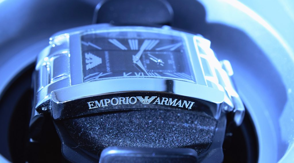 Um relógio Emporio Armani está fotografado de lado, estando em um expositor, sob uma luz azulada.