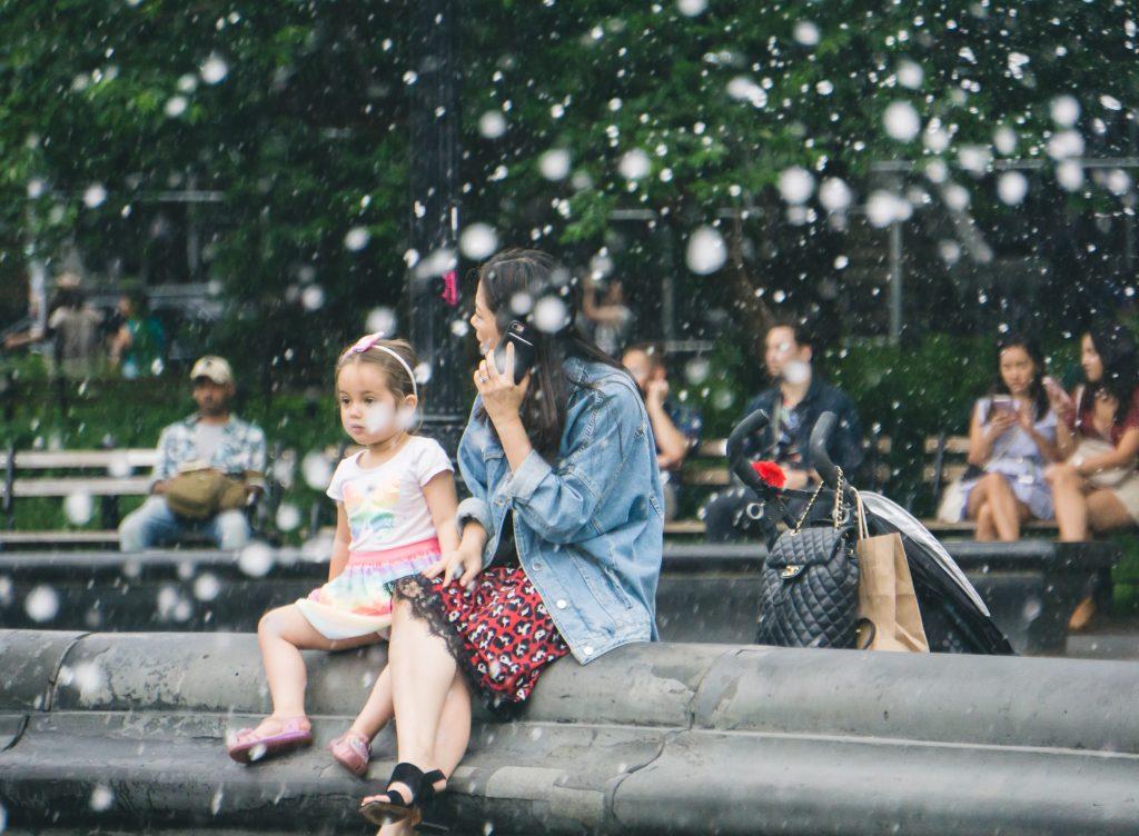 Mãe e filha sentadas em um parque.