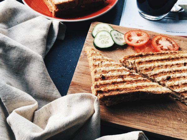 Imagem de sanduiche com vegetais cortados e copo de café