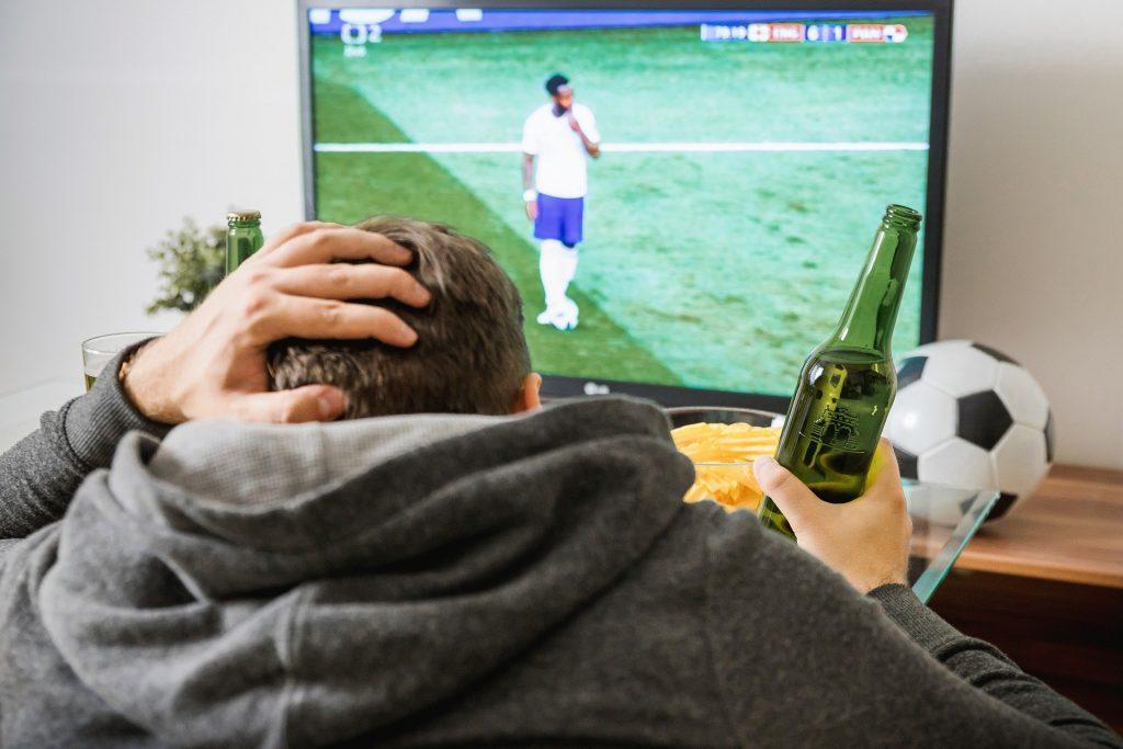 Imagem de homem assistindo uma partida de futebol em uma TV LG
