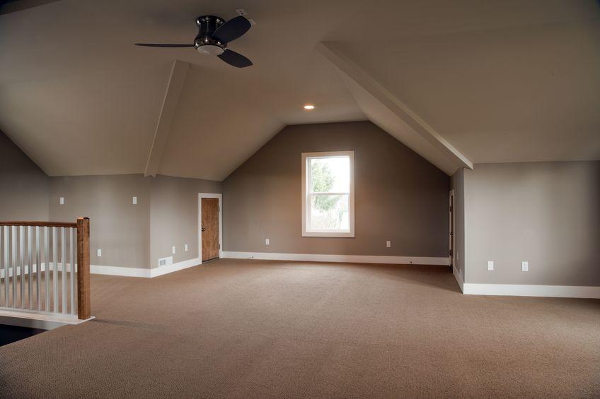 Imagem de uma sala vazia com um ventilador de teto ao centro.