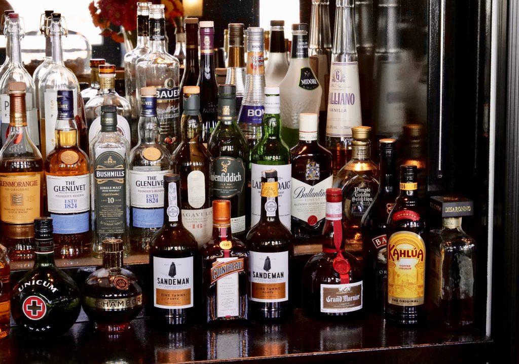 imagem de uma estante de bebidas, repleta de rótulos de uísques e outros destilados.