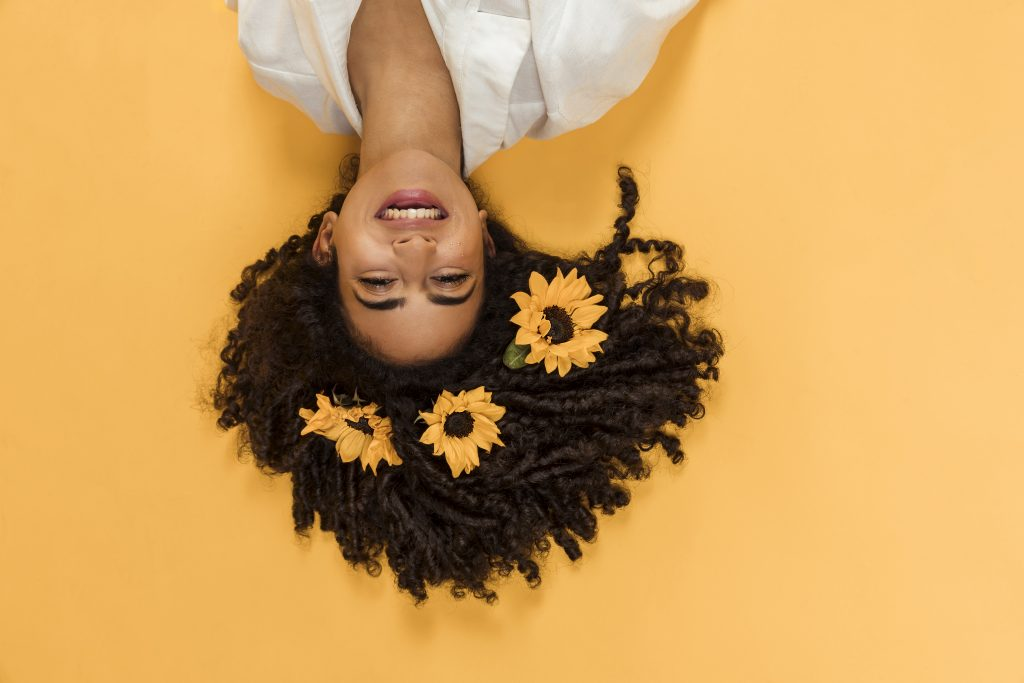 Mulher morena de cabelos cacheados com flores amarelas e deitada em um chão amarelo.