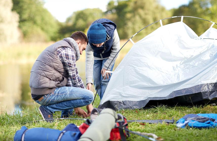 Imagem mostra duas pessoas, um adulto e uma criança, montando uma barraca na grama.