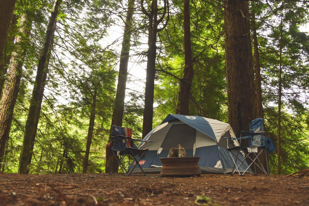 Imagem mostra uma barraca montada no meio de uma floresta, com duas cadeiras dobráveis montadas em sua frente.