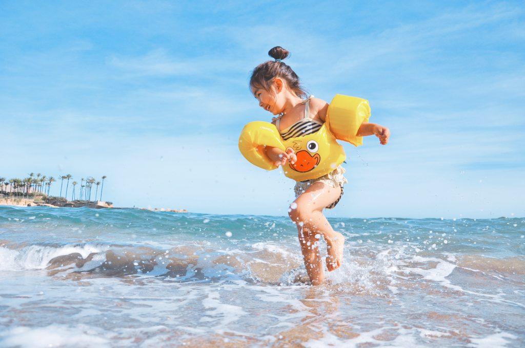 Na foto uma menina com boia brincando no mar.