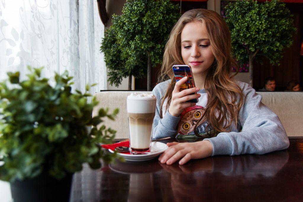 Imagem de uma menina fotografando o café.