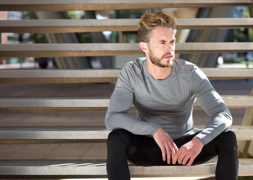 Homem sentando usando camiseta de manga longa.