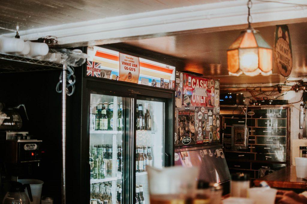 Imagem foca numa larga cervejeira de um estabelecimento comercial, ao lado de uma cafeteira.