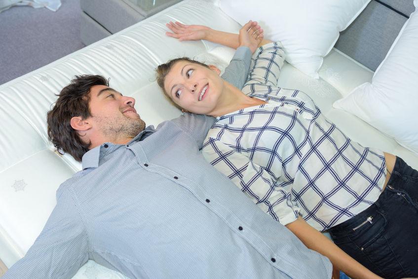 Imagem mostra um casal deitado numa cama. Eles trocam olhares, enquanto a mulher apoia sua cabeça no braço do homem.