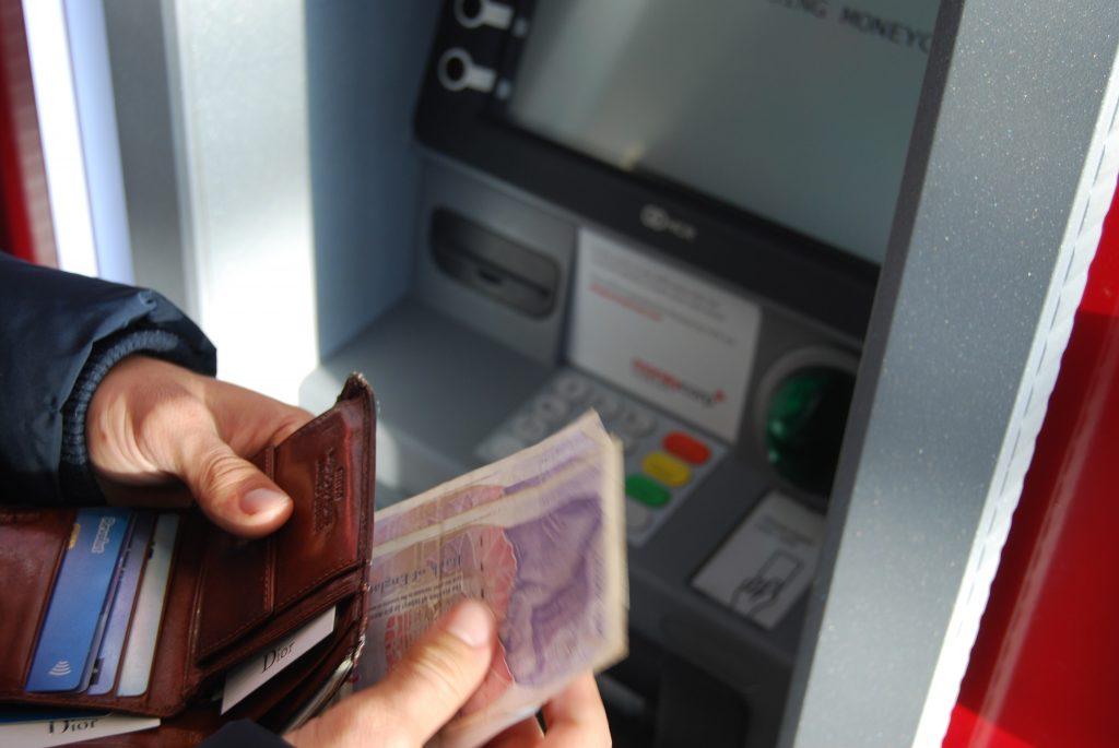Homem sacando dinheiro de caixa eletrônico e guardando na carteira.