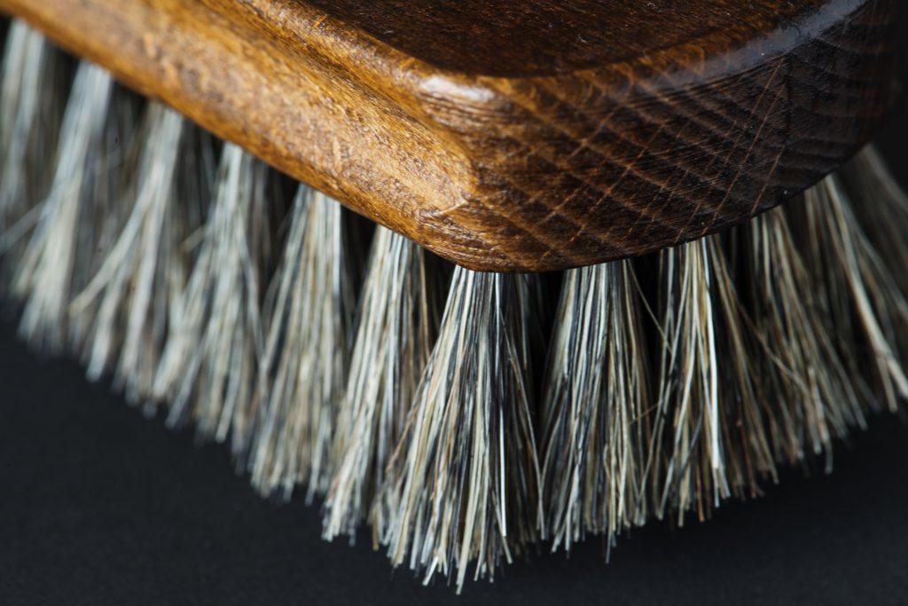 Escova raquete de madeira com cerdas naturais vista de perto em cima de uma superfície preta