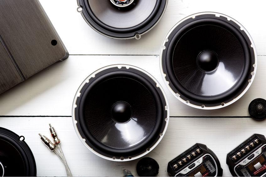 Imagem mostra uma composição de várias peças de equipamentos sonoros sobre uma mesa, com dois alto-falantes alinhados ao centro.