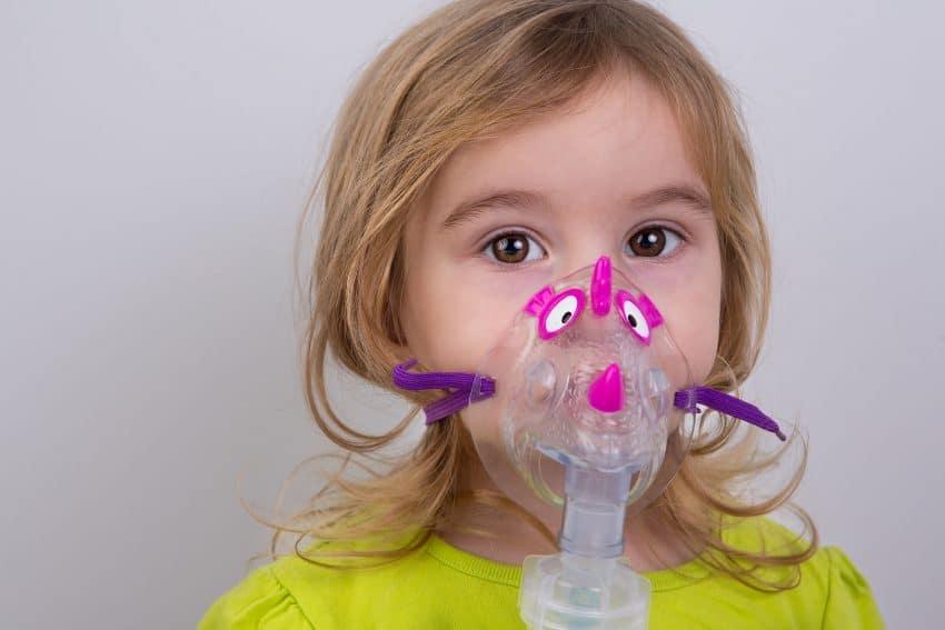 Na foto uma menina com uma máscara de nebulização.