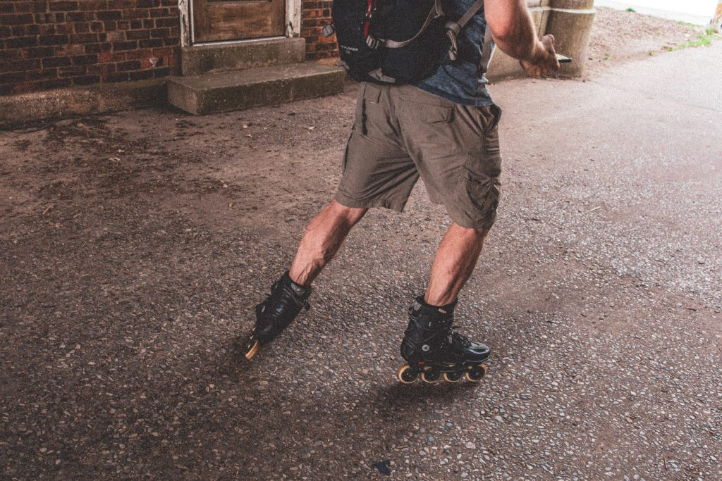 Imagem mostra um homem, mostrado no quadro abaixo do seu tronco, patinando num pavimento de concreto, enquanto tecla no seu smartphone.