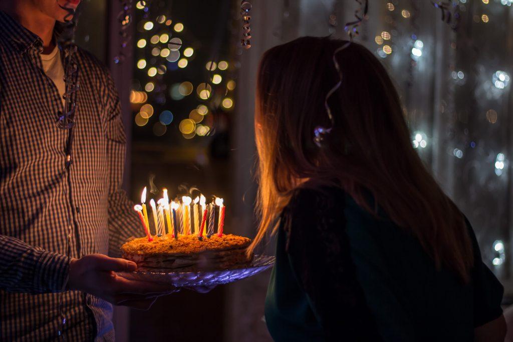 Na foto uma mulher apagando as velinhas de um bolo.