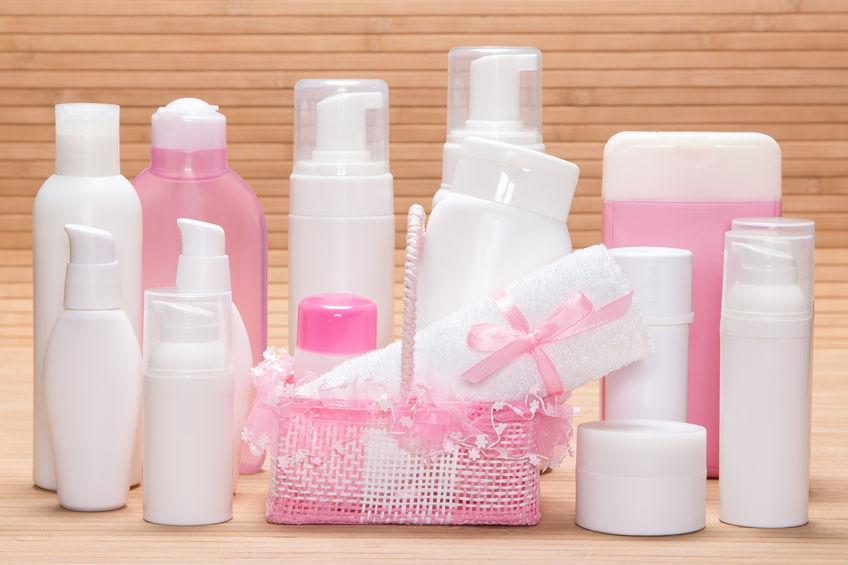 Três embalagens de shampoo brancas organizadas da maior pela menor em uma superfície branca com fundo azul