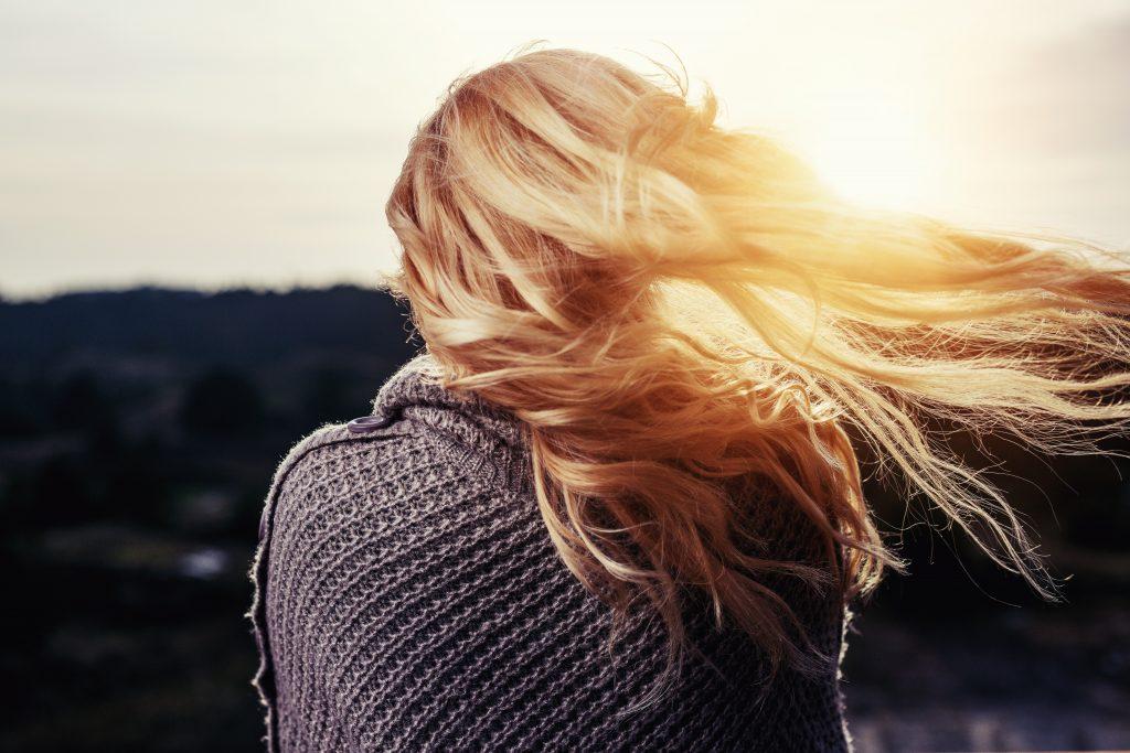Foto de uma mulher loira de costas, com cabelos ao vento e contra o sol, vestindo roupa de crochê.