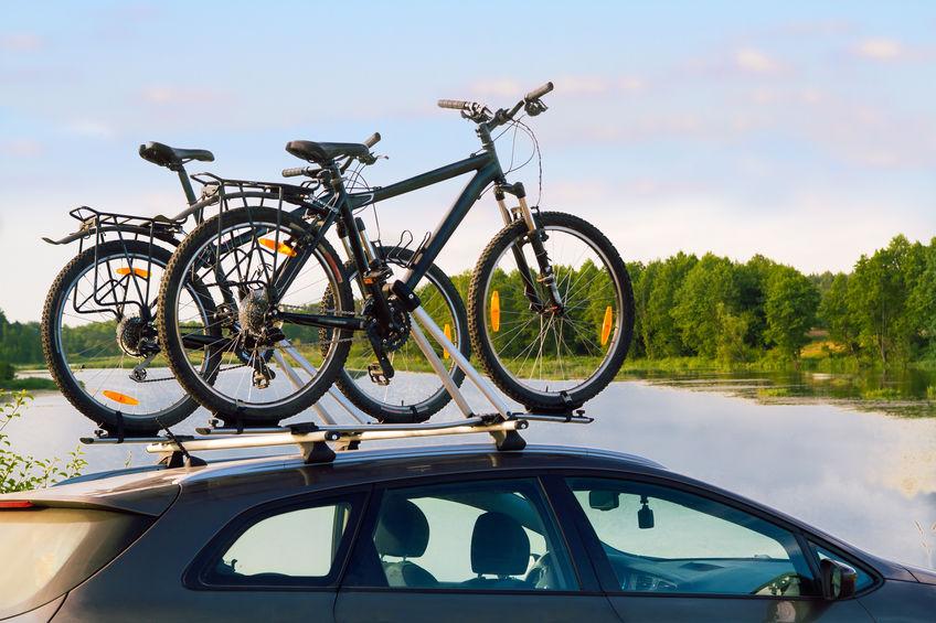 Imagem mostra apenas o teto de um carro que carrega, via suporte, oito bicicletas.