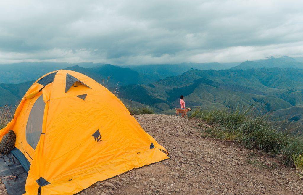 Imagem mostra, em primeiro plano, uma barraca montada sobre um terreno rochoso. Em segundo plano, uma mulher e seu cachorro no alto de um monte, observando as montanhas da paisagem.