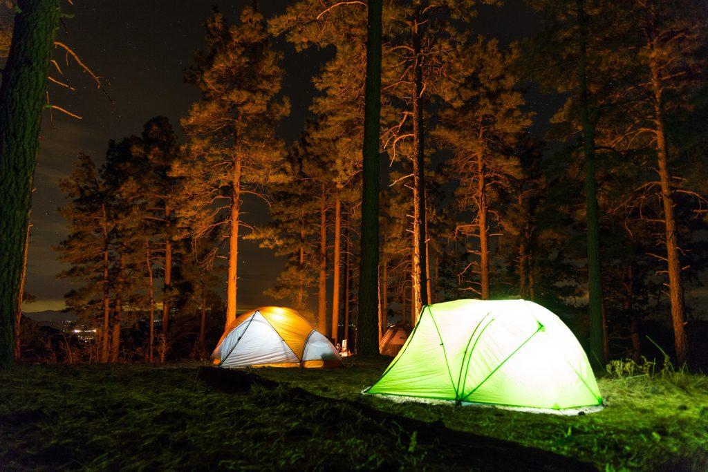Imagem mostra duas barracas iluminadas por dentro, montadas no meio de uma floresta, à noite. Luzes