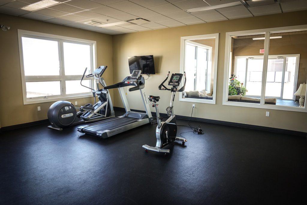 Imagem mostra uma pequena sala de musculação, ocupada por três máquinas, sendo uma delas uma bicicleta ergométrica.