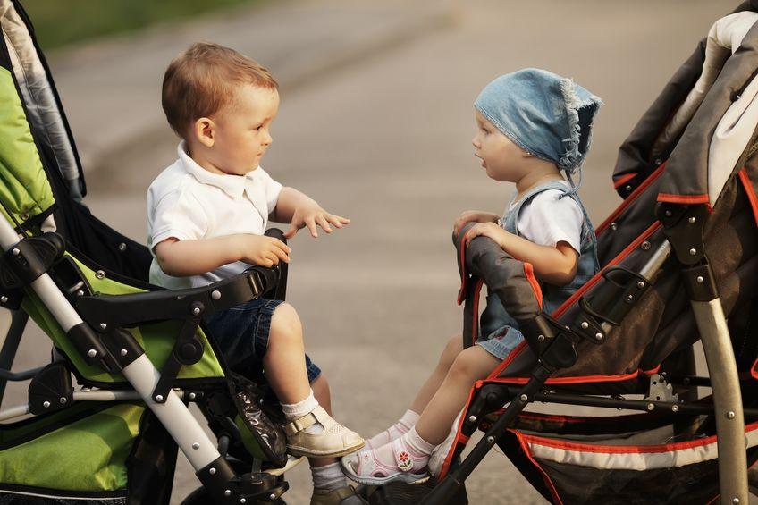 Um carrinho de bebê de frente para o outro com crianças de olhando.