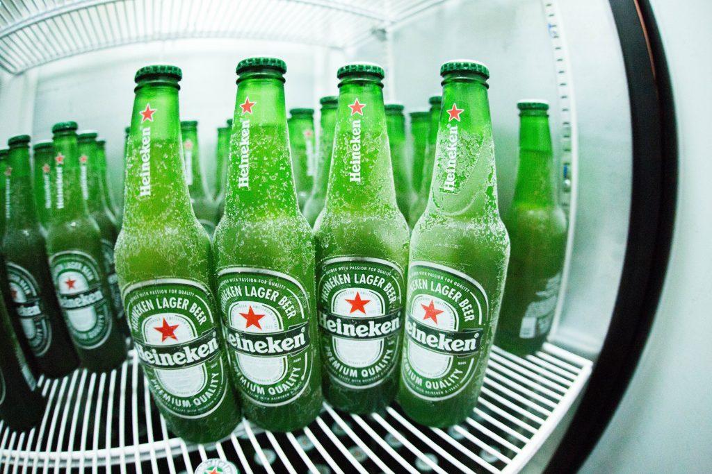 """Retrato de lente """"olho de peixe"""" foca em uma fileira de garrafas de cerveja """"nevadas"""", com outras garrafas desfocadas ao fundo, todas sobre uma prateleira de uma cervejeira, que está com a porta fechada."""