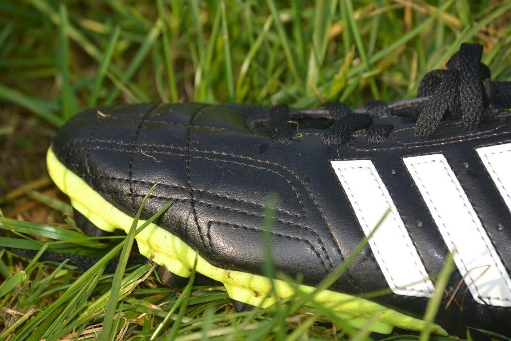 magem mostra em plano detalhe o cabedal do pé direito de uma chuteira preta da Adidas, que está apoiada numa grama alta..