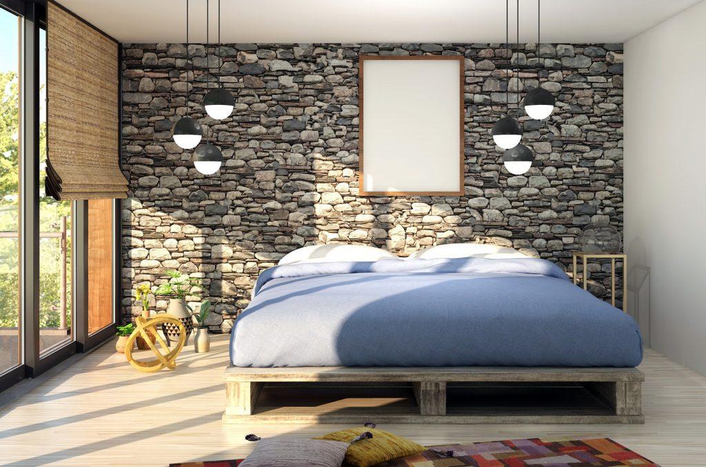 Imagem mostra uma cama de casal num quarta iluminado, com uma parede de pedras ao fundo.