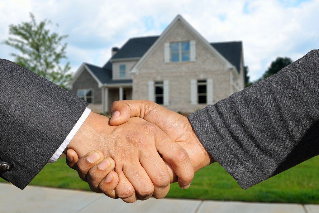 Dois homens apertando a mão em frente a casa.
