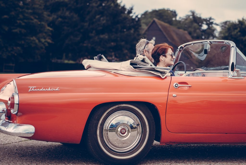 Casal em carro conversível.